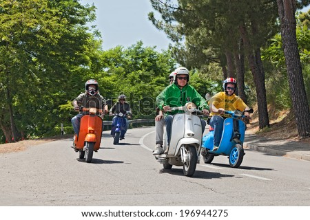 """MONTIANO, FC, ITALY - MAY 25: a group of bikers riding a vintage italian scooters Vespa and Lambretta on the italian country at the motorcycle rally """"Vespagiro"""" on May 25, 2014 in Montiano, FC, Italy - stock photo"""