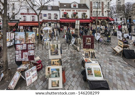 MONTMARTRE - MARCH 13: Artists easels and artwork set up in Place du Tertre in Montmartre, Paris on March 13, 2012. Montmartre attracted many famous modern painters in the early 20th century. - stock photo