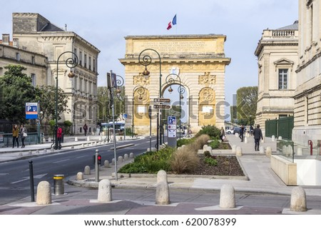 MONTPELLIER, FRANCE - MAR 31, 2017: Arc de Triumphe in Montpellier, dating from 1692, with surrounding buildings, people and traffic signs.