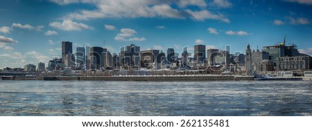 Montreal by a very cold day.  St-Lawrence river with ice with downtown Montreal in background  - stock photo