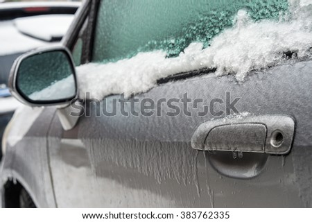 Montreal, CA, 29th February 2016. Car handle, mirror and window are covered with ice after icy rain. - stock photo