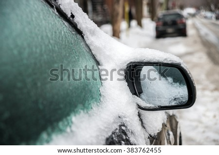 Montreal, CA, 29th February 2016. Car mirror and windows are covered with ice after icy rain. - stock photo