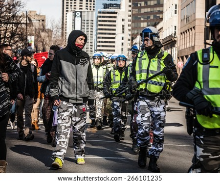 MONTREAL, CANADA   APRIL 02 2015: Riot in the Montreal Streets to counter the Economic Austerity Measures. Policeman and Protester looking each other in the eyes and wearing the same Army Pants - stock photo