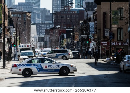 MONTREAL, CANADA  APRIL 02 2015: Riot in the Montreal Streets to counter the Economic Austerity Measures. Police Car in the Middle of the Street Blocking Traffic - stock photo