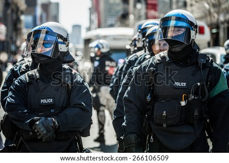 MONTREAL, CANADA   APRIL 02 2015: Riot in the Montreal Streets to counter the Economic Austerity Measures. Closeup of Cops Portraits Ready in case of Problem
