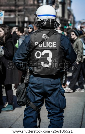MONTREAL, CANADA  APRIL 02 2015: Riot in the Montreal Streets to counter the Economic Austerity Measures. Detail of the Back of a Police Facing protesters.