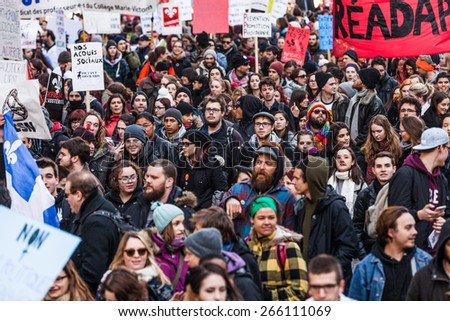 MONTREAL, CANADA   APRIL 02 2015: Riot in the Montreal Streets to counter the Economic Austerity Measures. Protesters Holding all kind of Signs, Flags and Placards in the Streets.