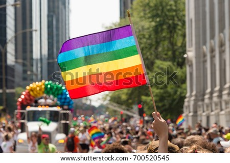 canada: Gay rainbow flag at Montreal gay pride parade with blurred participants in the