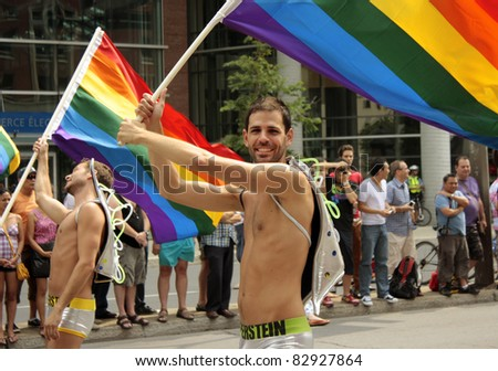 MONTREAL, CANADA - AUGUST 14: participants of parade bearing a flag at the Montreal Annual Gay Pride parade August 14, 2011, Montreal. - stock photo