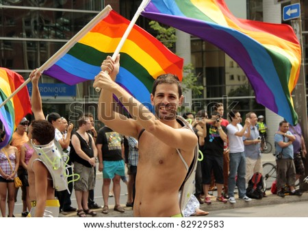MONTREAL, CANADA - AUGUST 14: participants of parade bearing a rainbow flag at the Montreal Annual Gay Pride parade August 14, 2011, Montreal. - stock photo