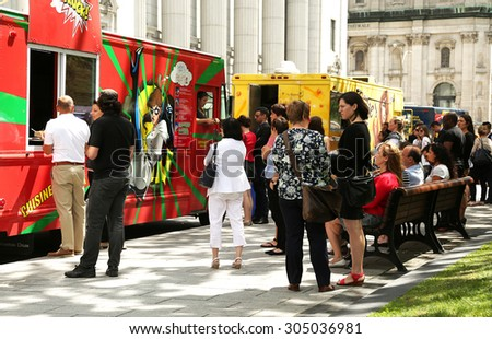 MONTREAL, CANADA - JULY 23, 2015: People waiting for their lunch at food trucks into the business area in Montreal, Quebec on july 23. - stock photo