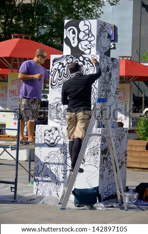 MONTREAL CANADA JUNE 15: Artists at work on a urban totem at the FIMA art festival on june 15 2013 in Montreal Canada - stock photo