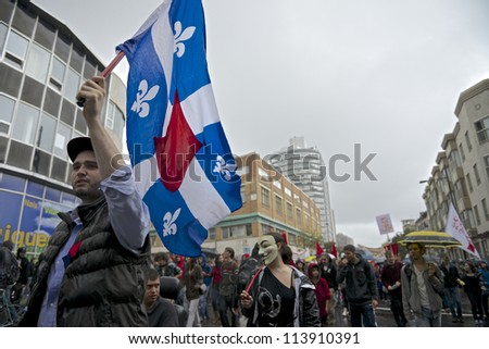 MONTREAL, CANADA - SEPTEMBER 22: An unidentified protester at a march demanding free education waves a Quebec flag altered to show support for communism on September 22, 2012 in Montreal. - stock photo