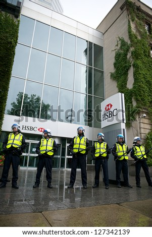 MONTREAL, CANADA - SEPTEMBER 22: Riot police protect an HSBC bank from protesters taking part in a demonstration demanding free college education on September 22, 2012 in Montreal - stock photo
