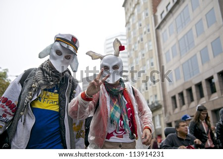 MONTREAL, CANADA - SEPTEMBER 22: Two unidentified protesters conceal their faces with masks during a march demanding free education on September 22, 2012 in Montreal. - stock photo