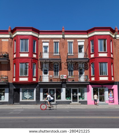 MONTREAL, CANADA  - 17TH MAY 2015: Colorful buildings along Avenue des Pins in Montreal during the day. People can be seen. - stock photo