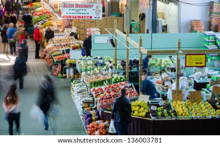 MONTREAL-CIRCA APRIL 2013: People buy groceries at Jean-Talon Market, the largest outdoor public market in North America. Circa April 2013, in Montreal - stock photo