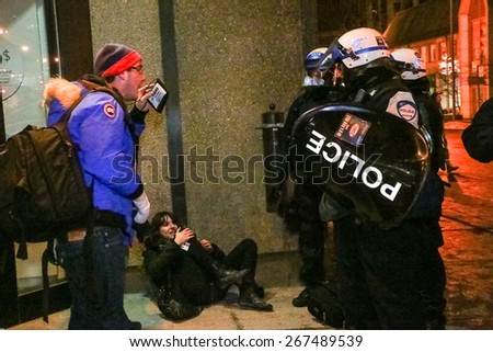 MONTREAL - MARCH 27: Police shove a woman to the ground as a man holds up a press pass in protest during a chaotic student demonstration in Montreal. - stock photo