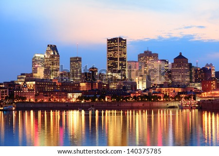 Montreal over river at sunset with city lights and urban buildings - stock photo