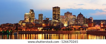 Montreal over river panorama at dusk with city lights and urban buildings - stock photo