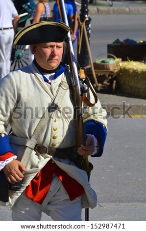 MONTREAL QUEBEC CANADA AUGUST 24: Man as soldier re-enacting New France period in Old Montreal, Pointe-a-Calliere's 18th Century Public Market on august 24 2013 in Montreal Canada - stock photo