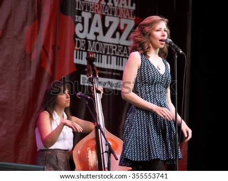 Montreal Quebec Canada - July 4 2014 - Boston swing pop quartet Lake Street Dive on stage in concert outdoors Festival International Jazz featuring female bass guitarist and singer - stock photo