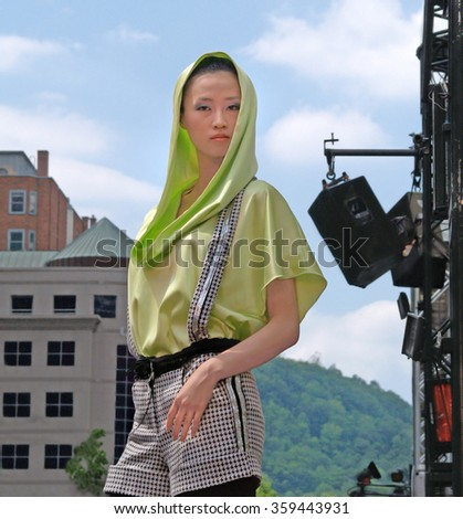 Montreal Quebec Canada - June 10 2007 - Fashion model Oriental Chinese young glamorous female beauty runway green silk head wear at  public festival mode & design stage outdoor
