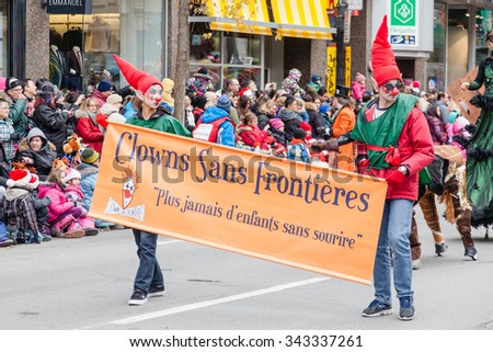 MONTREAL, QUEBEC, CANADA - NOVEMBER 21, 2015 : Elves holding a sign in the 65th edition of the Santa Claus Parade Destination Centre-ville (Defile du Pere Noel) along Saint Catherine Street. - stock photo