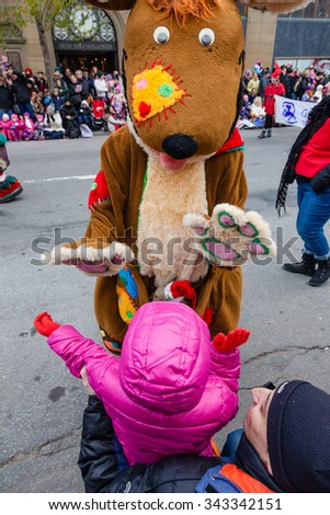 MONTREAL, QUEBEC, CANADA - NOVEMBER 21, 2015 : Little girl high five with a person in kangaroo costume in 65th edition of the Santa Claus Parade (Defile du Pere Noel) along Saint Catherine Street. - stock photo
