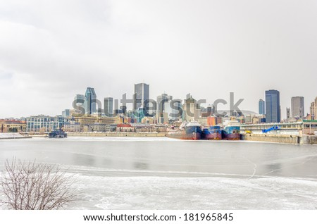 Montreal Skyline with an Iced St Lawrence River on a Winter Cloudy Day - stock photo