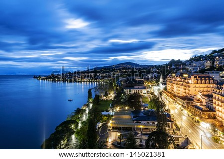 MONTREUX - MAY 19: Night view of Le Montreux Palace Hotel a five star luxury hotel built in 1906 and Montreux Music & Convention Centre (2m2c) and coastline in Montreux in Switzerland on May 19, 2013 - stock photo