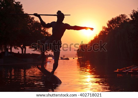 Monument on the lake: a warrior with a spear trying to reach the sun at sunset. West Lake, Hangzhou, China.