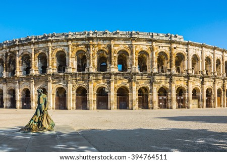Monument to bullfighter installed in the square. Roman amphitheater in Nimes, Provence. Photo taken fisheye lens - stock photo