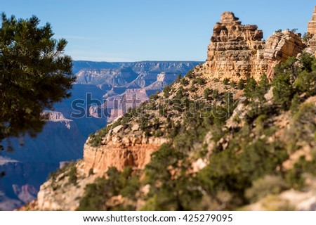 Monumental rock cliffs of the Grand Canyon forests with clear blue sky  - stock photo