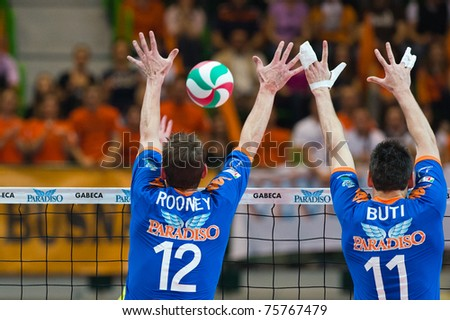 MONZA, ITALY - APRIL 20: Rooney and Buti ( Gabeca)  get a wall against the ball in Volley Gabeca Monza ( Blue) vs Volley Modena ( Yellow) -Italian Volley League on 2011 April, 20 in Monza (Italy)