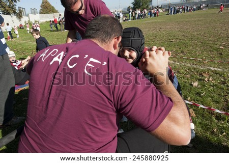 MONZA, ITALY-OCTOBER 25, 2010: dad supporting his son playing a mini rugby match, in Monza.