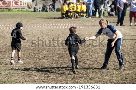 MONZA, ITALY-OCTOBER 25, 2009: young rugby player giving high five to his woman coach, during a children rugby tournament, in Monza. - stock photo