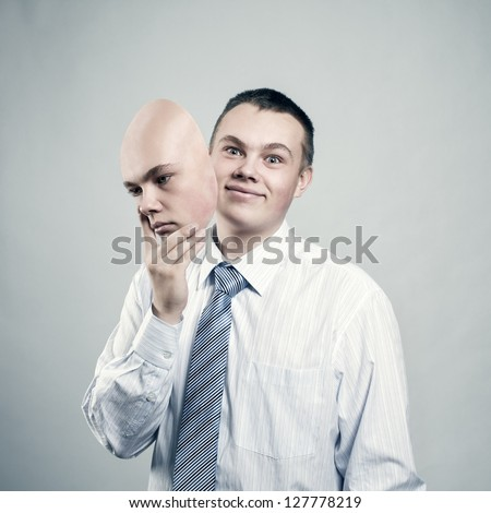 Mood changes. Businessman removes the mask from the face of a bad mood - stock photo