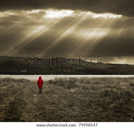 moody and atmospheric image of an unknown walker in a bright red coat looking at a dramatic sky with sun beams across a lake. Toned image with a color pop. - stock photo