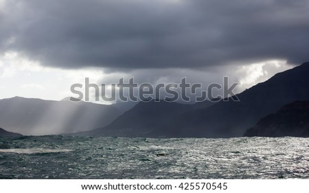 Moody and atmospheric rough seas off the coast of Hout Bay, South Africa with table mountain and Cape Town in the distance