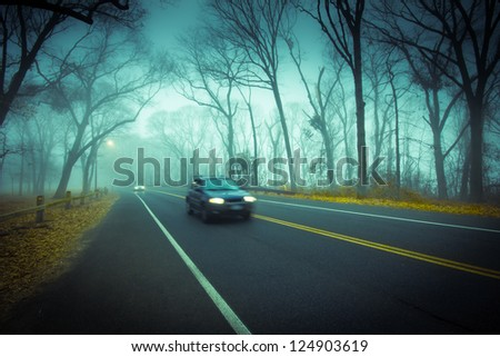 Moody, cold, foggy drive with car on road