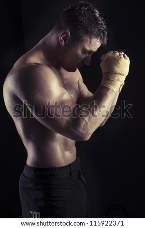 Moody dark portrait of a handsome sexy male bodybuilder standing sideways with his hands raised to his forehead flexing his arms muscles - stock photo