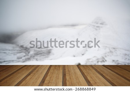 Moody dramatic low cloud Winter landscape in mountains with snow on ground with wooden planks floor - stock photo