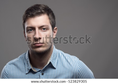 Moody dramatic portrait of serious young man in blue shirt looking at camera with copyspace