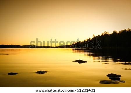 moody nightfall an a rocky shore - stock photo