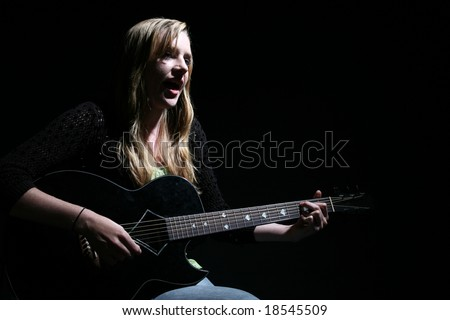 moody picture of beautiful woman playing guitar and singing - stock photo