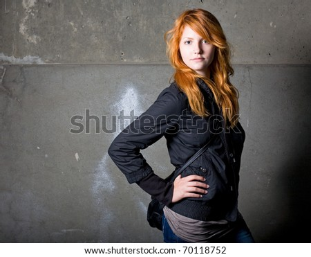 Moody portrait of a beautiful fashionable young redhead girl.