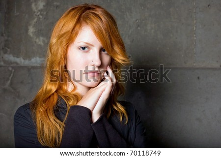 Moody portrait of a beautiful fashionable young redhead girl with sad facial expression.