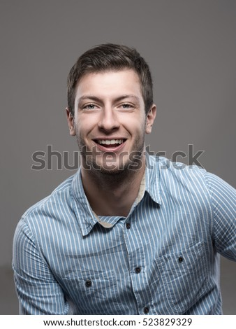 Moody portrait of confident successful ceo in blue shirt smiling and looking at camera