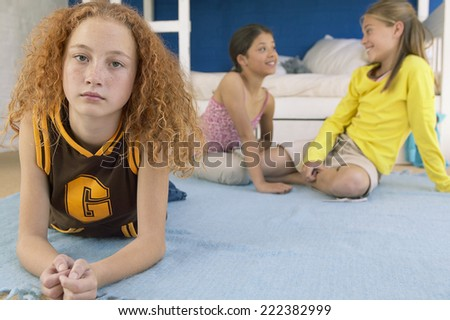 Moody preteen girl with friends - stock photo